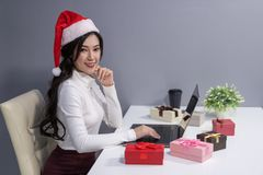happy woman wear santa hat and christmas gift with labtop computer royalty free stock photos