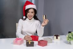 Happy woman wear santa hat holding credit card and christmas gif stock photos