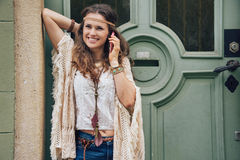 Happy woman wearing bohemian style clothes talking cell phone. Happy woman wearing bohemian style clothes standing outside buildings in street and talking cell stock images