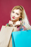 Happy Woman Wearing Bright Shirt is Holding a Lot of Shopping Colorful Bags. Amazing Blonde with Lond Hair and Charming Royalty Free Stock Photography