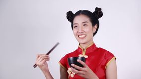 Woman wearing chinese cheongsam dress with chopsticks and bowl stock footage