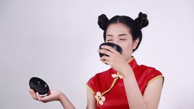 Woman wearing chinese cheongsam dress with chopsticks and bowl stock video footage