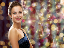 Happy woman wearing earrings over christmas lights. People, holidays, jewelry and glamour concept - happy beautiful woman wearing pearl earrings over christmas Royalty Free Stock Photography