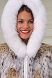 Happy woman wearing a fur coat Stock Image