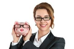 Happy woman wearing glasses holding funny piggybank Stock Photos