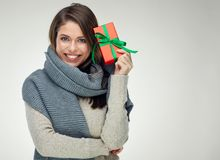 Happy woman wearing gray scarf holding red gift box. Isolated portrait on white background Stock Image