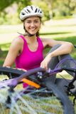 Happy woman wearing helmet with bicycle in park Royalty Free Stock Images