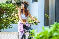 Happy woman wearing helmet riding bicycle in the summer. Happy asian woman wearing helmet riding bicycle in the summer stock images