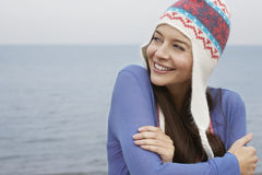 Happy Woman Wearing Knit Hat Standing Against Sea Royalty Free Stock Photography
