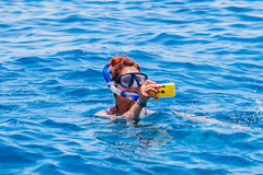 Happy woman wearing a mask in the sea, along with a camera Royalty Free Stock Images
