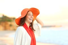Happy woman contemplating ocean on the beach. Happy woman wearing an orange picture hat contemplating ocean on the beach Royalty Free Stock Image