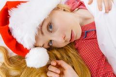 Happy woman wearing pajamas and Santa Claus hat Stock Photography