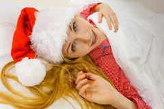 Happy woman wearing pajamas and Santa Claus hat Royalty Free Stock Photography