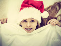 Happy woman wearing pajamas and Santa Claus hat Stock Images