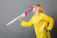 Happy woman wearing raincoat holding closed umbrella. Good mood during rainy day. Happy blonde woman wearing yellow raincoat holding closed umbrella Stock Photography