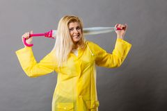 Happy woman wearing raincoat holding closed umbrella. Good mood during rainy day. Happy blonde woman wearing yellow raincoat holding closed umbrella Stock Images