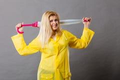 Happy woman wearing raincoat holding closed umbrella Stock Images