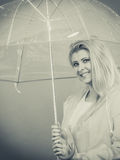 Happy woman wearing raincoat holding transparent umbrella. Good mood during rainy day. Happy blonde woman wearing raincoat holding transparent umbrella Royalty Free Stock Photo