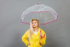 Happy woman wearing raincoat holding transparent umbrella. Good mood during rainy day. Happy blonde woman wearing yellow raincoat holding transparent umbrella Royalty Free Stock Images