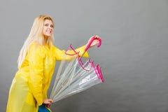 Happy woman wearing raincoat holding transparent umbrella. Good mood during rainy day. Happy blonde woman wearing yellow raincoat holding transparent umbrella Royalty Free Stock Image