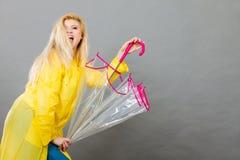 Happy woman wearing raincoat holding transparent umbrella. Good mood during rainy day. Happy blonde woman wearing yellow raincoat holding transparent umbrella Royalty Free Stock Photography