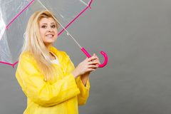 Happy woman wearing raincoat holding transparent umbrella. Good mood during rainy day. Happy blonde woman wearing yellow raincoat holding transparent umbrella Stock Photo