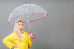 Happy woman wearing raincoat holding transparent umbrella. Good mood during rainy day. Happy blonde woman wearing yellow raincoat holding transparent umbrella Stock Image