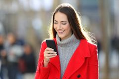 Woman walking and using a smart phone in winter Stock Photos