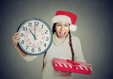 Happy woman wearing red santa claus hat holding clock gift box Stock Images