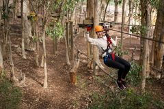 Happy woman wearing safety helmet riding on zip line in the forest royalty free stock image