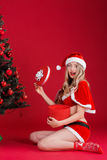Happy woman wearing santa claus clothes with Christmas gift. Portrait of happy woman wearing santa claus clothes with Christmas gift on red background Royalty Free Stock Photos