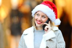 Woman calling on phone in christmas on the street Stock Photos