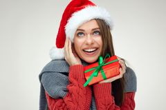 Happy woman wearing Santa hat holding gift box looking up. Portrait on white Stock Image