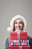 Happy woman wearing a Santa hat and holding gifts Stock Photos