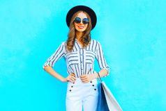 Happy woman is wearing a shopping bags, black hat, white pants. Over colorful blue background posing in the city Royalty Free Stock Images