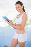 Happy woman wearing sportswear scrolling on tablet Stock Photo