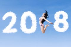 Happy woman with swimsuit and numbers 2018. Happy woman wearing swimsuit while flying with clouds shaped numbers 2018 in the blue sky Royalty Free Stock Image