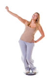 Happy woman wearing tracksuit standing on weighing machine Royalty Free Stock Photography