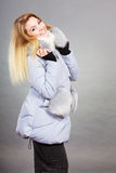 Happy woman wearing winter warm furry jacket. Seasonal fashion, clothes and clothing concept. Happy blonde woman wearing light winter warm furry coat perfect for Stock Photos
