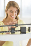 Happy Woman Weighing Herself On Balance Scale Stock Image