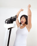 Happy Woman on Weight Scale Cheering stock photos