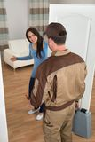 Happy woman welcoming plumber at home Stock Photo