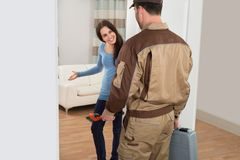 Happy woman welcoming plumber at home Royalty Free Stock Photos