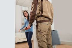 Happy woman welcoming plumber at home Royalty Free Stock Photography