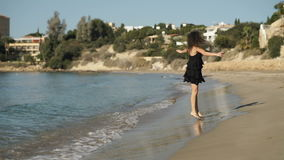 Happy woman in wet dress fooling around on the beach stock video footage