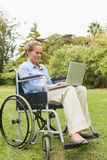 Happy woman in a wheelchair using a laptop Royalty Free Stock Image