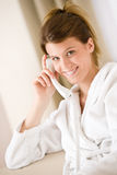 Happy woman in white bathrobe with phone Stock Photography