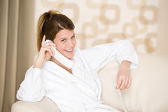 Happy woman in white bathrobe with phone Stock Images