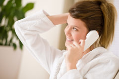 Happy woman in white bathrobe with phone home Stock Photos