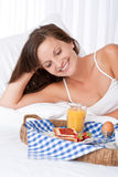 Happy woman in white bed having breakfast Stock Photography